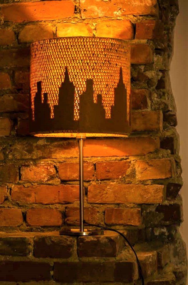 Zapalona lampa z motywem miasta stojąca na czerwnej cegle
