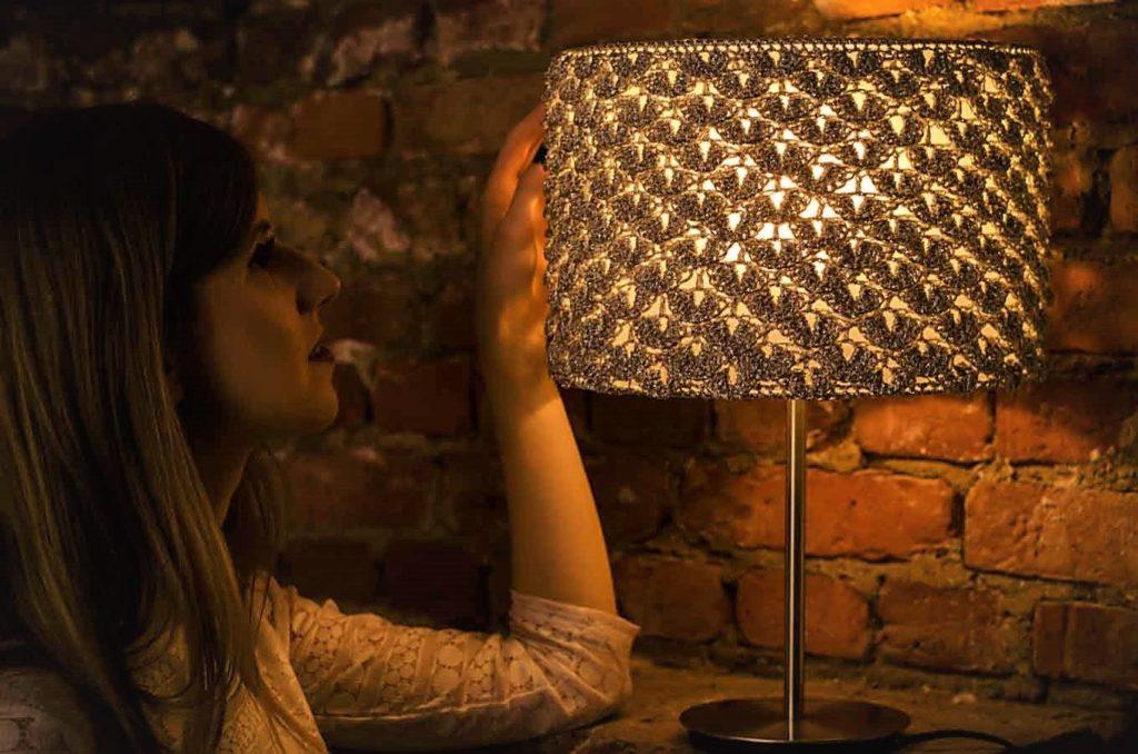 kobieta patrzy na zapaloną lampę
