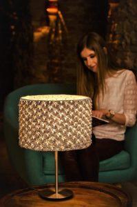 lampa zrobiona na szydełku i kobieta czytająca książkę