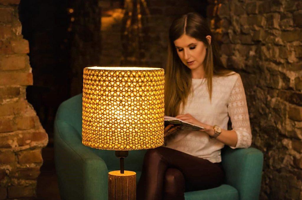 dziewczyna czyta książkę przy zapalonej, złotej lampie