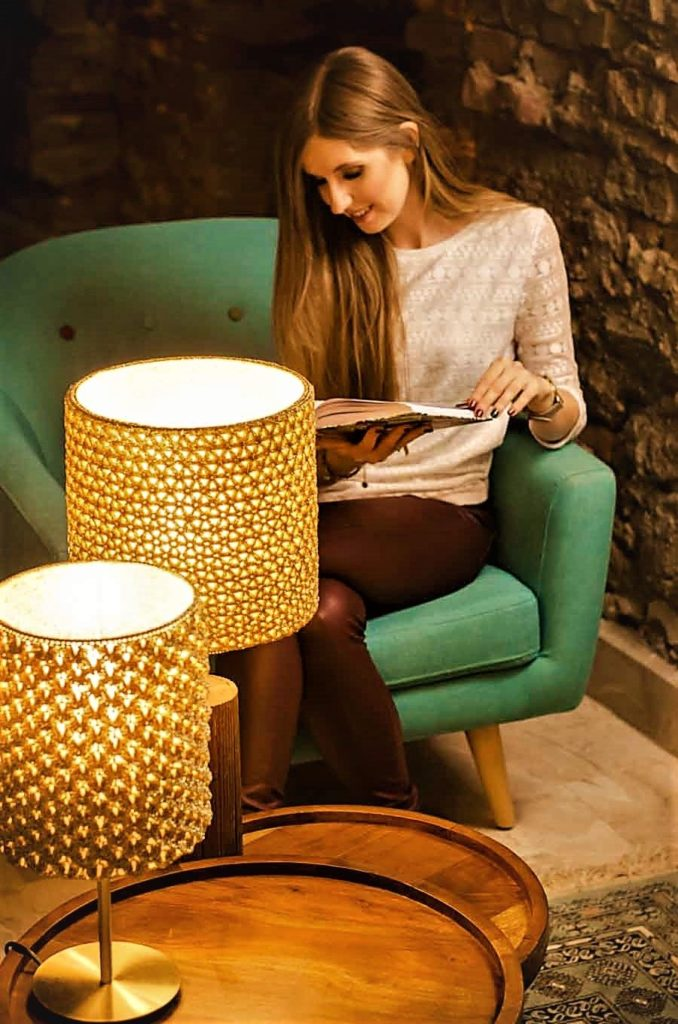 kobieta czyta przy zapalonych złotych lampach