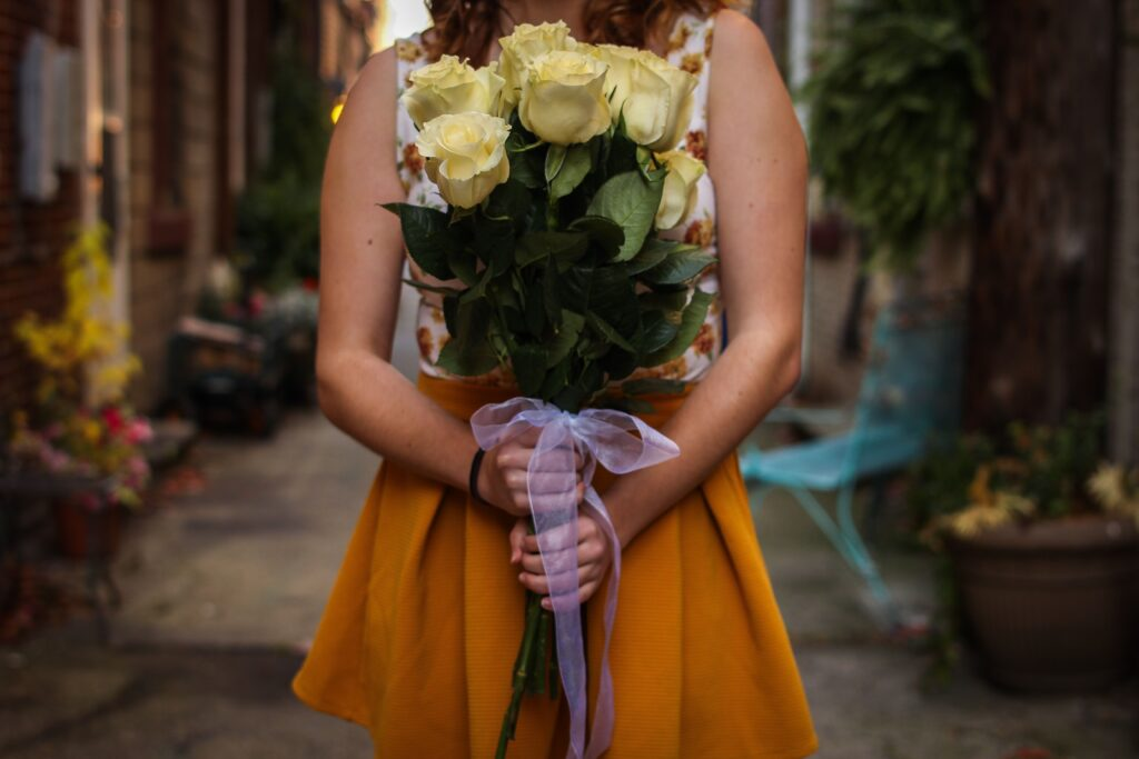 kobieta trzyma bukiet białych róż