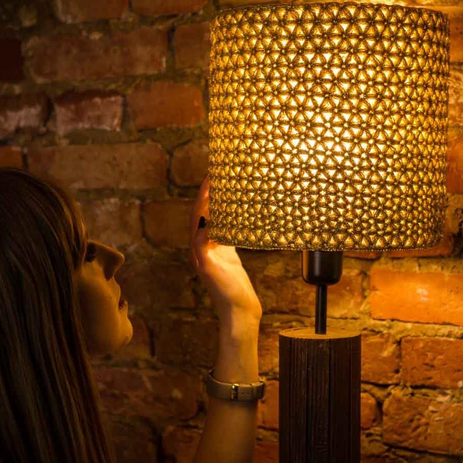 kobieta patrzy na zapaloną złotą lampę stołową