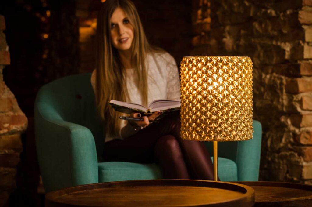 dziewczyna z książką, czyta przy złotej lampie zrobionej na szydełku
