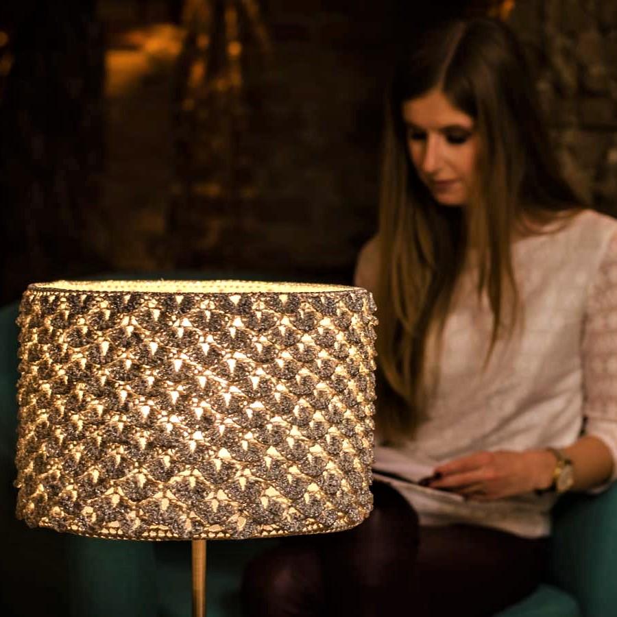 srebtna lampa stołowa i kobieta czytająca książkę