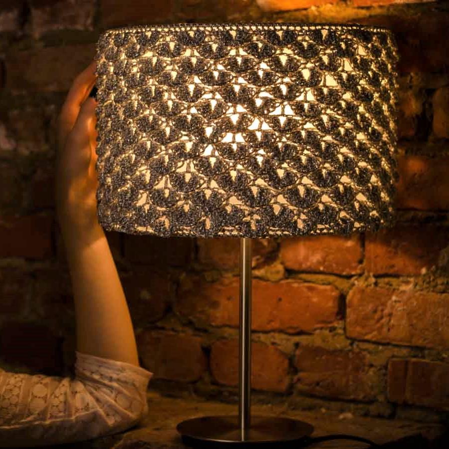 kobieca dłoń dotyka srebrnej lampy