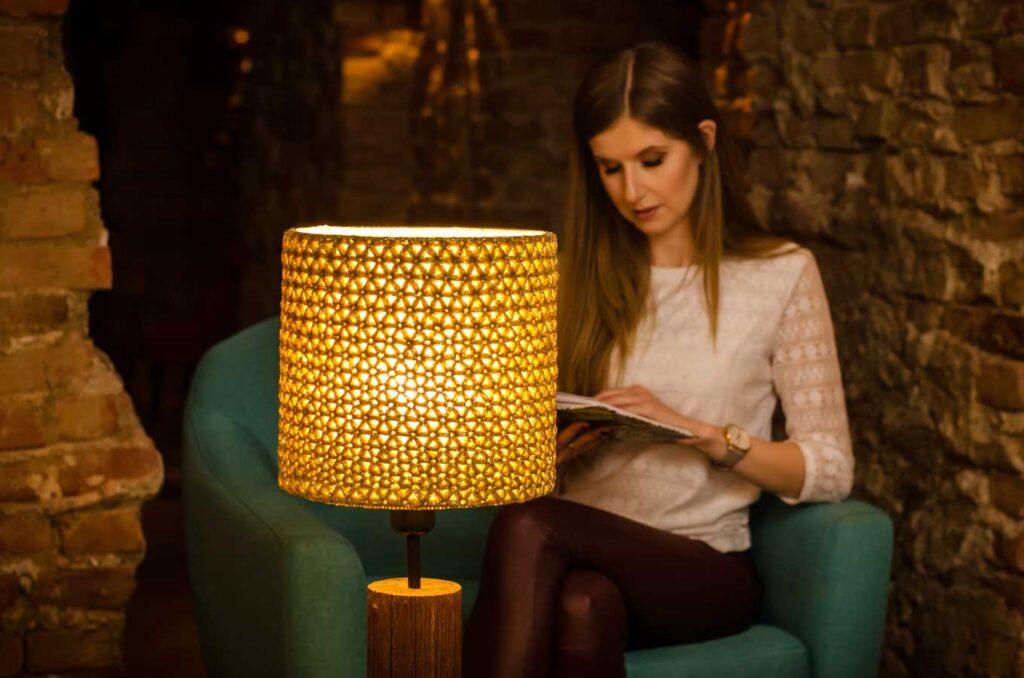 dziewczyna siedzi na fotelu, czyta książkę przy złotej lampie stołowej